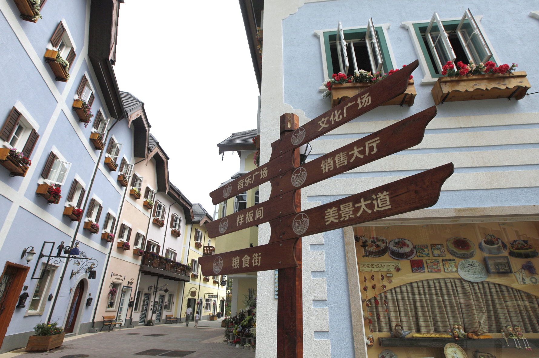 A Chinese road sign is seen at the replica of Austria's UNESCO heritage site, Hallstatt village, in China's southern city of Huizhou in Guangdong province June 1, 2012. Metals and mining company China Minmetals Corporation spent $940 million to build this controversial site and hopes to attract both tourists and property investors alike, according to local newspaper reports. REUTERS/Tyrone Siu (CHINA - Tags: BUSINESS SOCIETY TRAVEL)